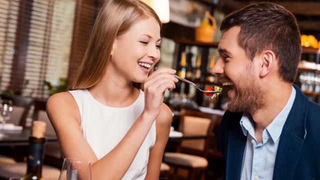 Um casal come alimentos afrodisíacos em um jantar romântico.